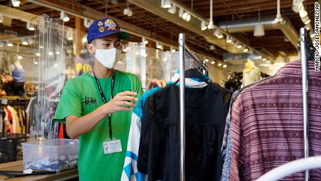 An employee sorts a clothing rack at 2nd Street second hand store Monday in the Fairfax district of Los Angeles.