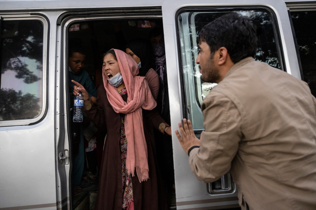 A woman yells for her family to hurry up as displaced Afghans from the northern provinces are evacuated from a makeshift IDP camp in Share-e-Naw park to various mosques and schools.