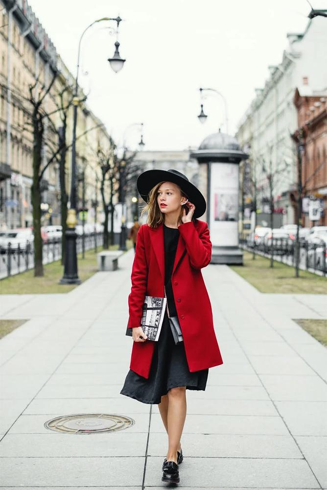 Woman in Red Coat and Black Skirt Walking on Sidewalk